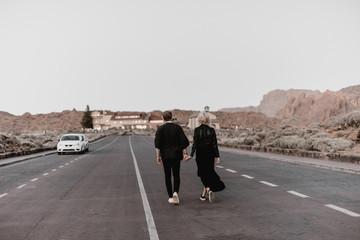 Couple walking on asphalt road