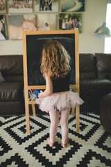 Vertical photo of child with a chalkboard