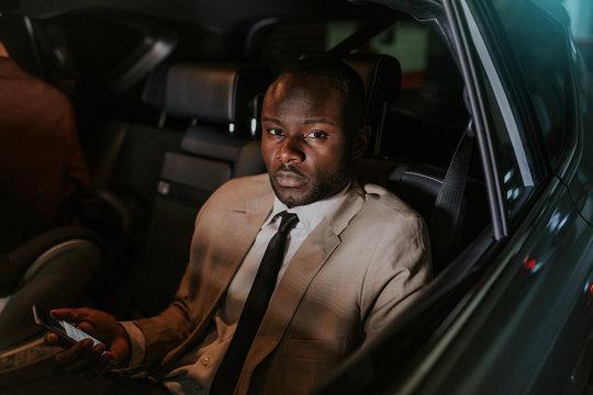 Black businessman inside the car holding a phone