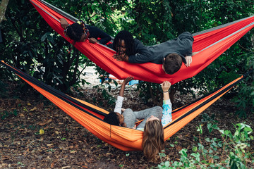 Black and Caucasian kids chilling out in colorful hammocks