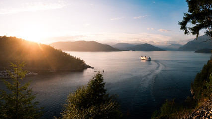 A ferry ship cruising out of a harbour in a mountain pass at sunset