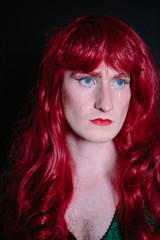 Non binary guy in drag wearing green dress and red wig