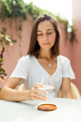 Young woman drinking water at cafe