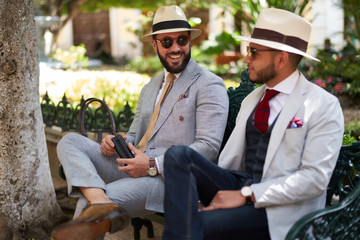 Two happy stylish men in a park