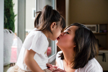 Asian Mother Kissing Her Daughter at Home