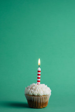 Cupcake with birthday candle on a green background