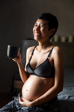 Smiling pregnant woman with mug sitting on bed