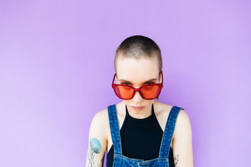 Portrait of stylish woman with crewcut on the purple background