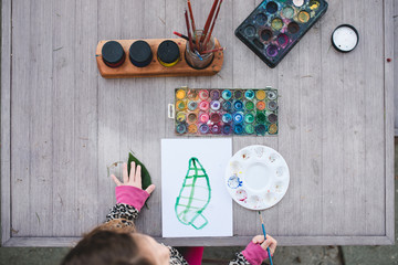 Overhead shot of a child studying and painting a leaf