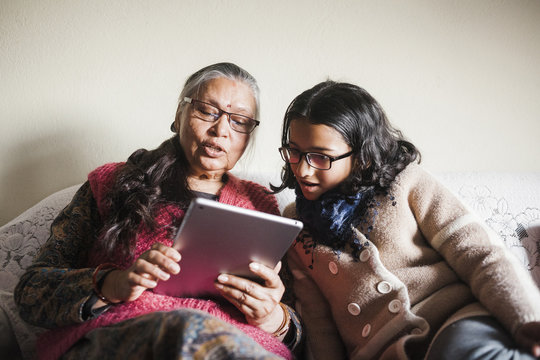 A young girl and a retired senior woman at home looking at a tablet.