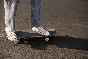 casual stylish person standing on skateboard in the street