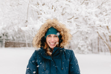 Portrait of a smiling beautiful woman with snow falling