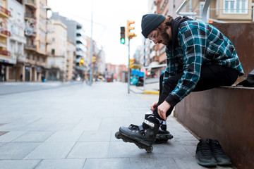 Hipster young man sitting on the bench while putting his roller skates on the street.