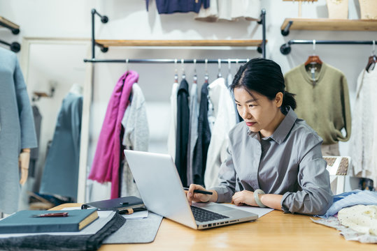 Business owner working at a laptop in clothing store