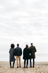 Four people on the beach against overcast sky.