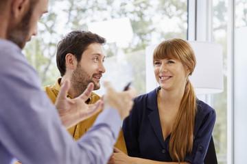 Advisor Explaining Smiling Couple In Office