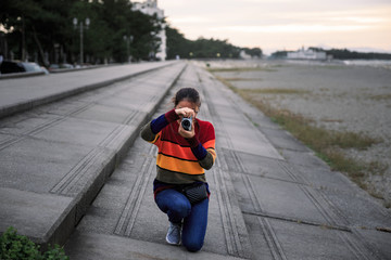 Girl crouching on concrete steps to take picture
