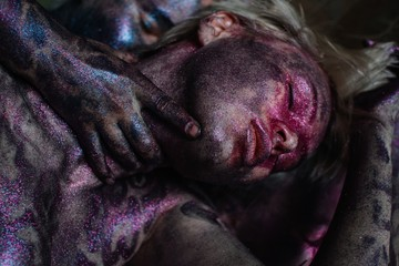 Young woman with violet body art and dreamy closed eyes laying on reflecting background and crop hands touching her neck