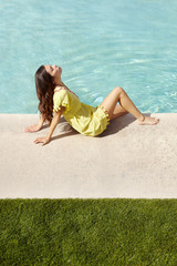 Beautiful Hispanic woman relaxing poolside at luxury resort in Palm Springs