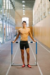 Confident sportsman posing in gym