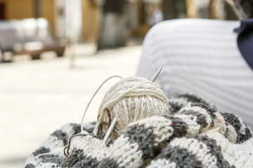 Hairs of wool, knitting needles and woolen clothes are prepared for work. Close-up