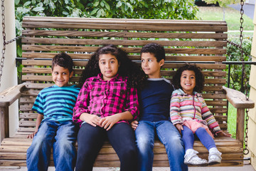 Four interracial siblings sitting on a bench together