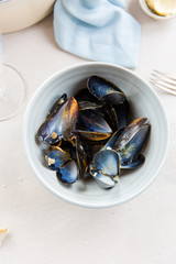 The remains of a meal of mussels. Shells and almost empty wine glass.