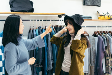 Young lady trying hat in clothing store
