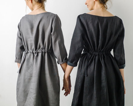 Rear view of women in dresses holding hands
