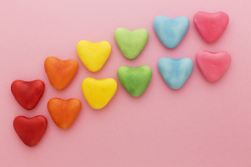 Heart-shaped multi-colored candy ordered in rainbow colors and shape on a pink background