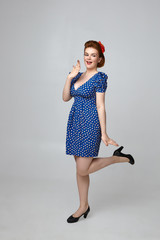 Wow. Vertical picture of attractive fashionable female model wearing 60s retro outfit having excited facial expression, covering mouth and lifting up one leg. Flirty pin up girl posing in studio