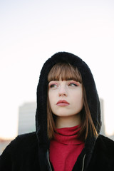 Beautiful young girl in black coat