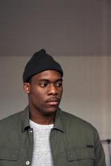 Emotionless black man in hat