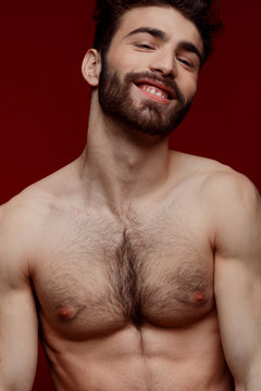 Handsome shirtless strong man portrait over red background