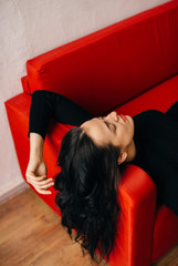 brunette woman lying on the  red sofa