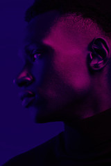 African American man portrait under blue and purple lights - Ultraviolet