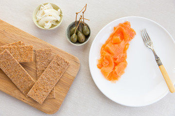 A scandinavian inspired light meal of smoked salmon, scandinavian crackers, pickled vegetable and caper berries.