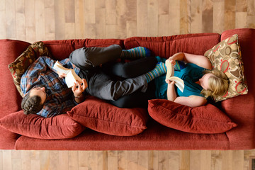 Overhead view couple quiet moment reading on sofa in ski chalet