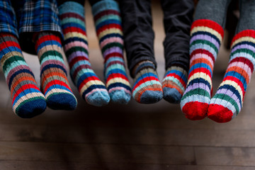 Four pairs of feet in warm colorful knit socks