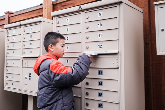 Asian Kid Putting Mails Inside the Mailbox