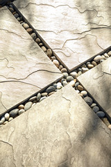 Sun on concrete pavers with river stones in between