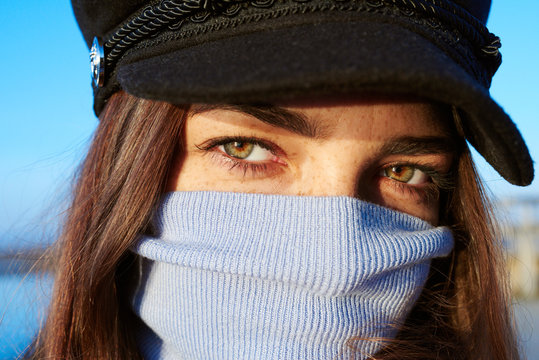 Girl in cap with sweater neck on her face.