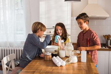 Children having fun mixing ingredient in the kitchen