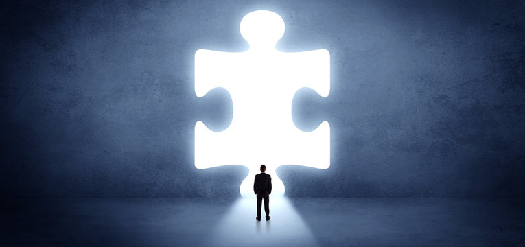 Businessman  standing and looking to a big puzzle piece
