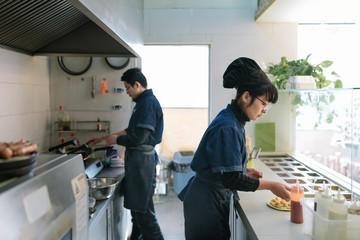 Pizza shop worker working in kitchen