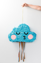 cute pastel paper party cloud pinata behind a white wall