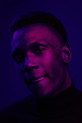 African American man portrait under blue and purple lights - Ultraviolet