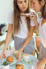Girls making photo of summer breakfast at phones