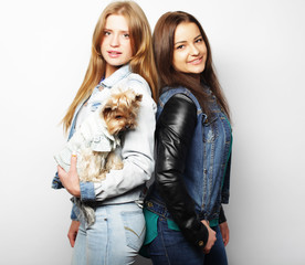 lifestyle and people concept: Two young girls friends standing together and holding dog