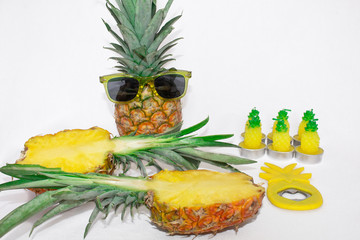 Two pineapples in dark glasses and a pineapple cut on a wooden board.